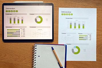Diagramme auf einem Tablet und einem Ausdruck. Darunter ein Notizbuch mit einem Kugelschreiber