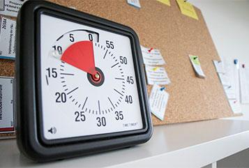 Eine Scrum-Uhr vor einem Korkboard
